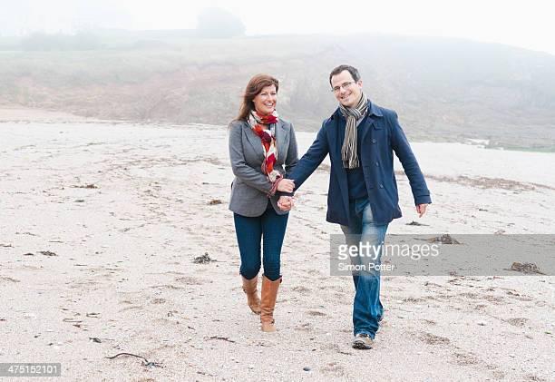 Couple walking on beach, Thurlestone, Devon, UK