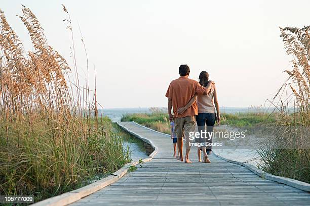 couple walking on beach walkway - hilton head stock pictures, royalty-free photos & images