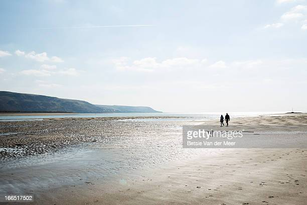 Couple walking on beach with dog, North wales.