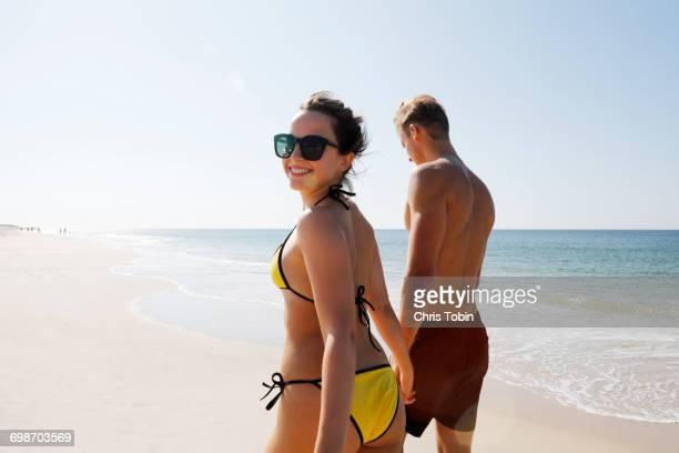 Couple walking on beach woman looking back