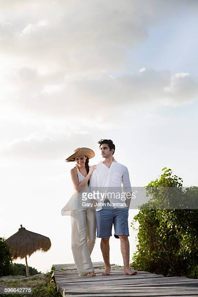 Couple walking on boardwalk at the beach.