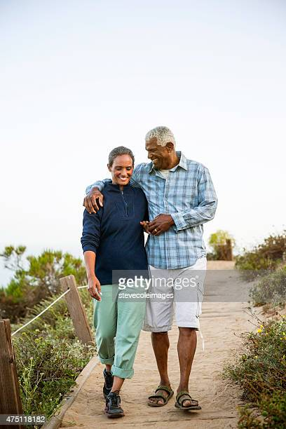 couple walking on boardwalk. - mature couple stock pictures, royalty-free photos & images