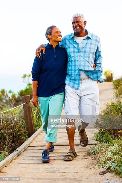 Couple walking on boardwalk.