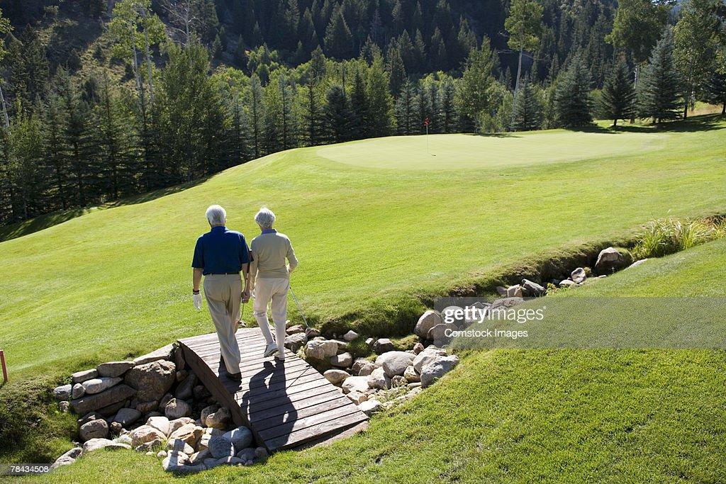 Couple walking on bridge on golf course : Stockfoto