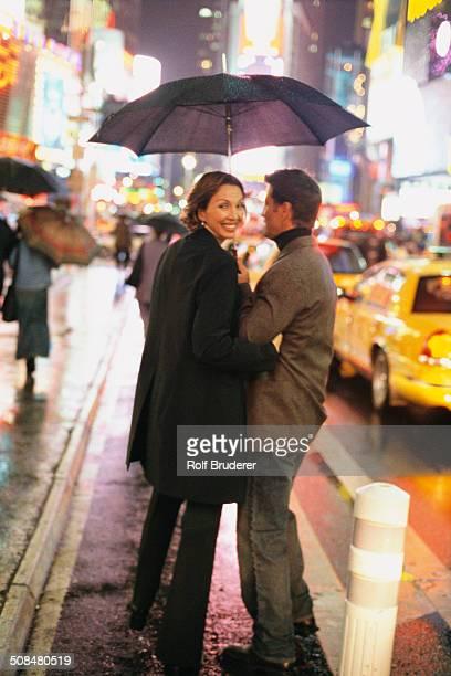 Couple walking on city street at night, New York City, New York, United States