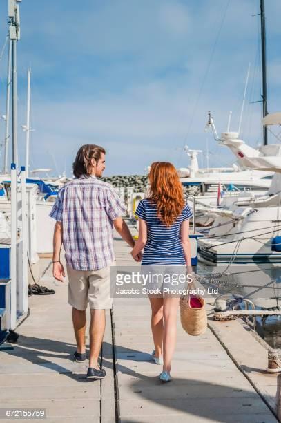 Couple walking on dock at marina