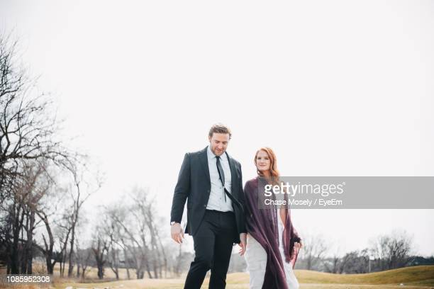 Couple Walking On Field Against Clear Sky
