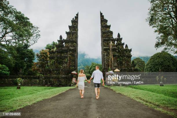 couple walking on footpath at gate against sky - indonesien stock-fotos und bilder