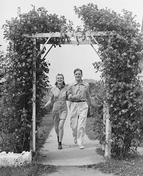 Couple walking on footpath towards rose covered pergola, (B&W)
