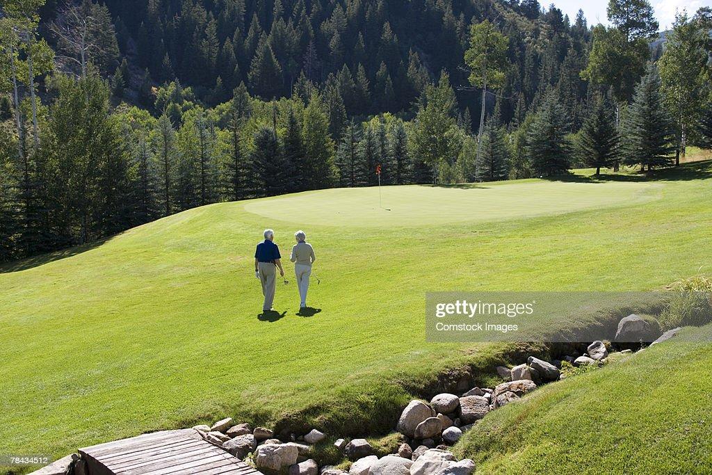 Couple walking on golf course : Stockfoto