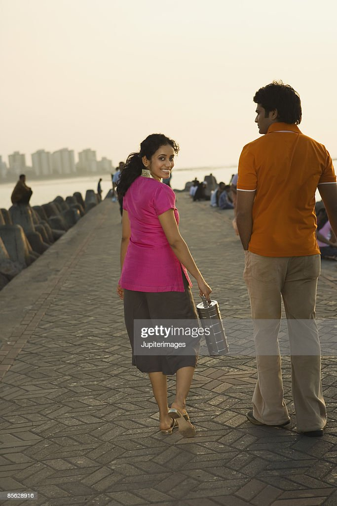 Couple walking on pier with tiffin : Stock Photo