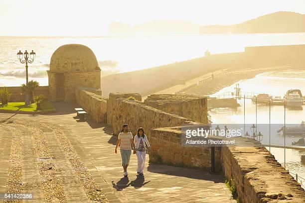 Couple walking on promenade in near city wall in Alghero