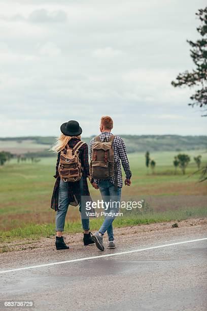 Couple walking on roadside by field against sky