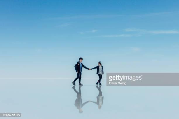 couple walking on salt flat against sky at salar de uyuni - ウユニ塩湖 ストックフォトと画像