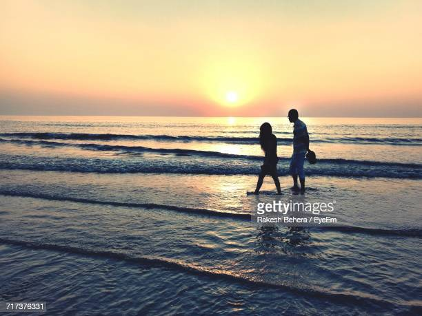 Couple Walking On Shore At Beach Against Sky During Sunset
