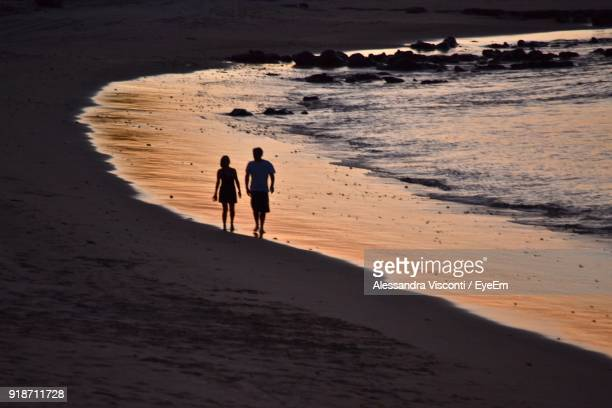 Couple Walking On Shore At Beach During Sunset