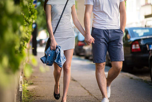 Couple walking on sidewalk with hand in hand - gettyimageskorea
