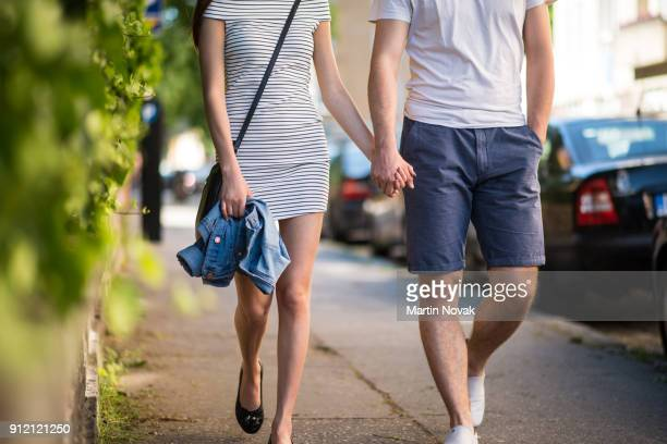 couple walking on sidewalk with hand in hand - couples dating stock pictures, royalty-free photos & images