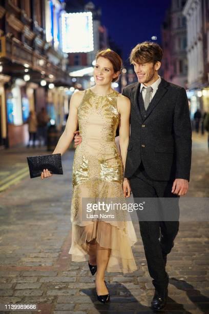 couple walking on street at night, london, uk - vestito da sera femminile foto e immagini stock