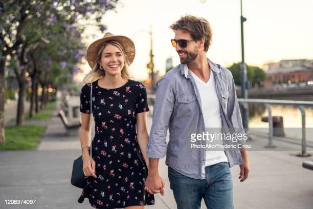 couple walking on street - pareja joven fotografías e imágenes de stock