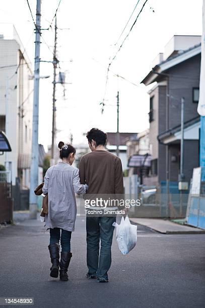 couple walking on street - ビニール袋 ストックフォトと画像