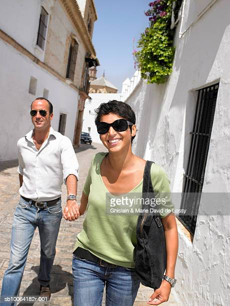 Couple walking on street, smiling