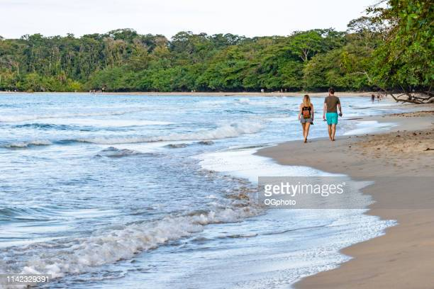 couple walking on the beach. - ogphoto stock pictures, royalty-free photos & images
