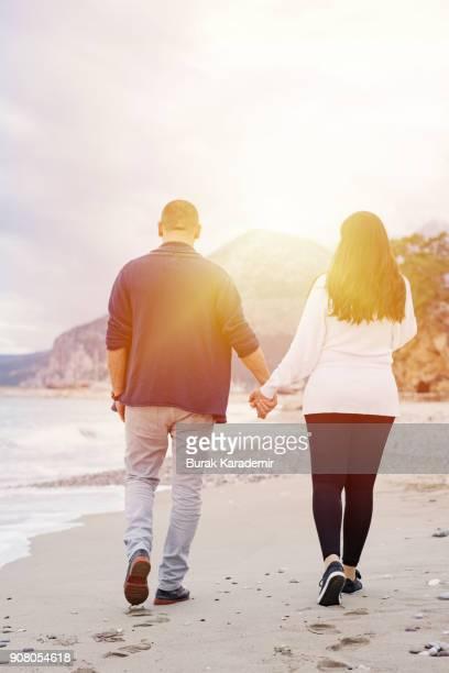 Couple walking on the beach, rear shot