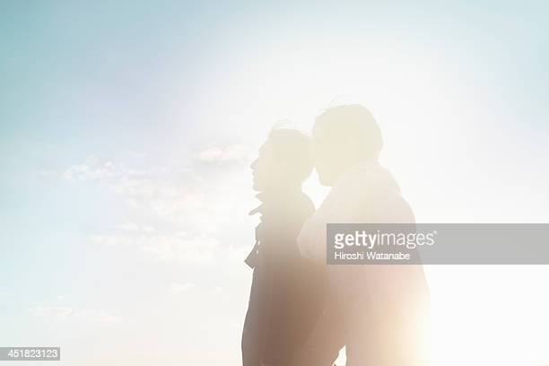 couple walking on the pavement at sunset - 希望 ストックフォトと画像