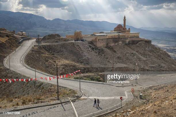 a couple walking on the road with isak pasa palace at the background,dogubayazit. - emreturanphoto stock pictures, royalty-free photos & images