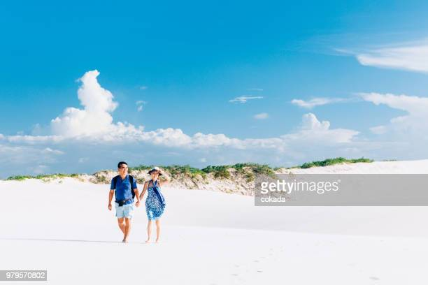 couple walking on the sand at the beach - lencois maranhenses national park stock pictures, royalty-free photos & images