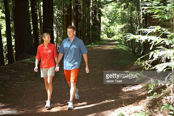couple walking on trail through redwoods - jason todd stock photos and pictures