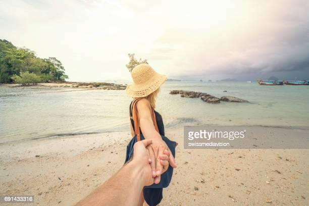 Couple walking on tropical beach- follow me