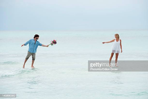 Couple walking on water towards each other, man holding out bouquet