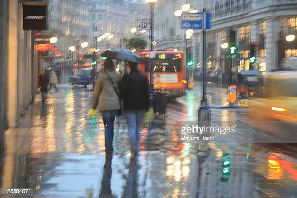 Couple walking on wet surface of street