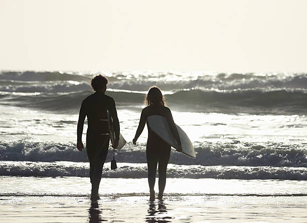 Couple walking out to sea with surfboards.