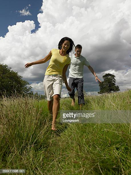Couple walking outdoors, smiling, low angle view