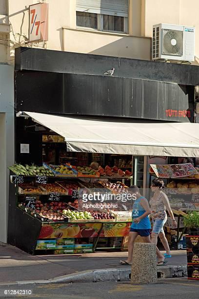 Couple walking past a Fruit shop