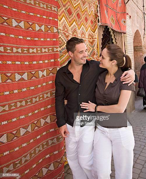 couple walking past carpet shop - hugh sitton foto e immagini stock