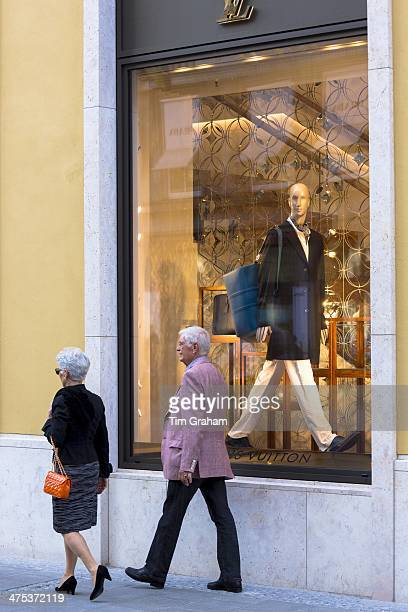 Couple walking past Louis Vuitton shop in Residenzstrasse in Munich Bavaria Germany