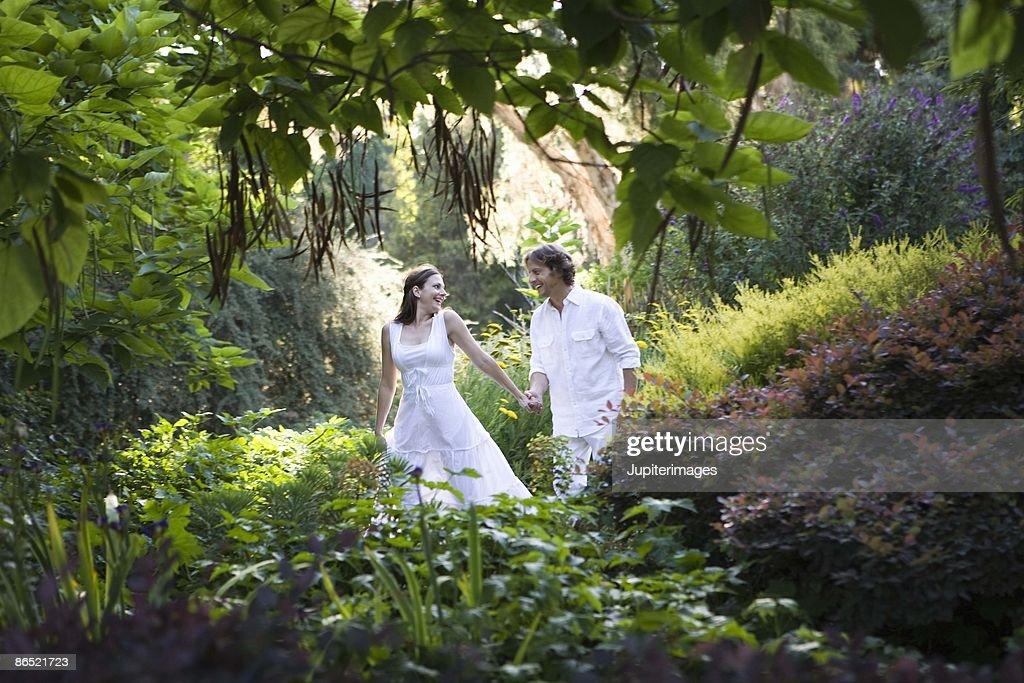 Couple walking through a garden : Stock Photo