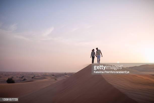 couple walking through desert. - ras al khaimah stock pictures, royalty-free photos & images