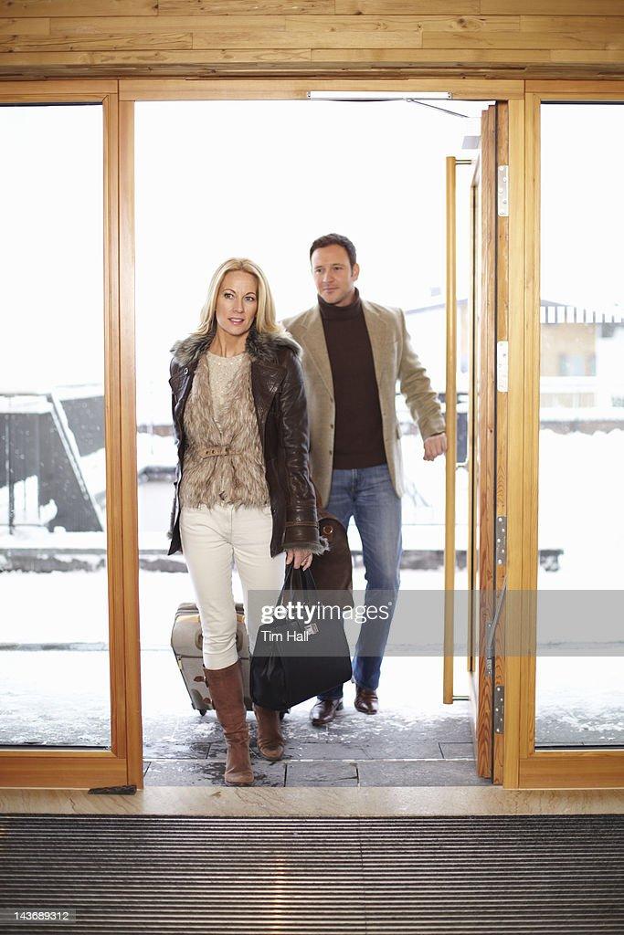 Couple Walking Through Hotel Front Doors Stock Photo