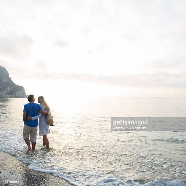 Couple walking through sea shallows