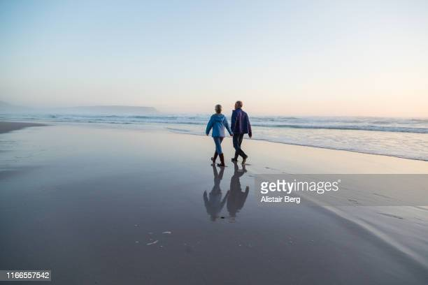 couple walking through shallow lagoon at sunset holding hands - semplicità foto e immagini stock