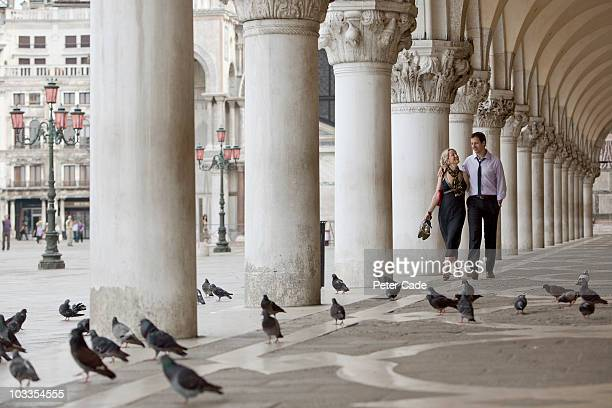 couple walking through St Marks Square, Venice