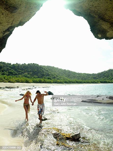 couple walking through surf on beach, smiling - antigua & barbuda stock pictures, royalty-free photos & images