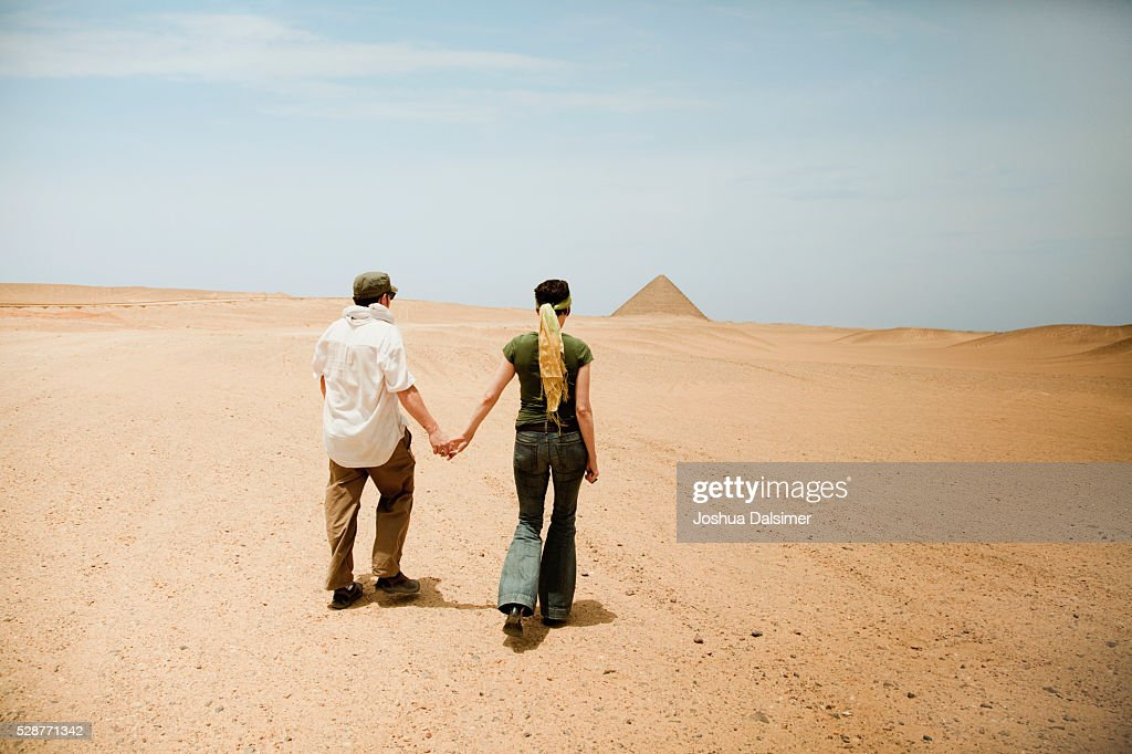 Couple walking through the desert : Stock Photo