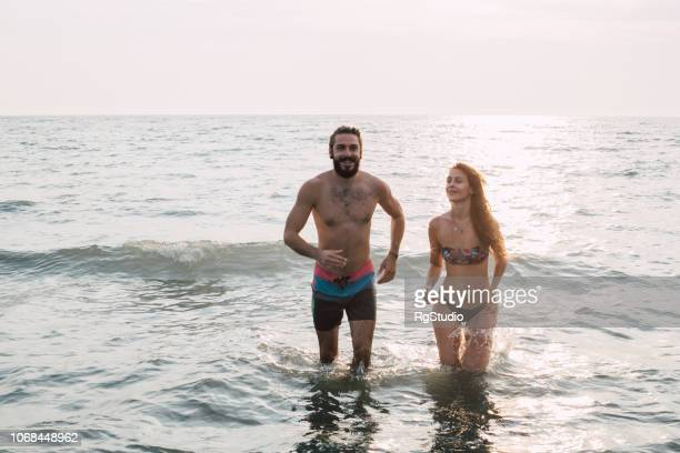 couple walking through the water - i love you stock pictures, royalty-free photos & images