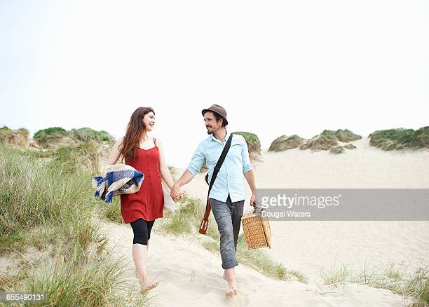 Couple walking to beach with picnic basket.